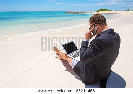 Businessman working with computer and talking on phone on the beach
