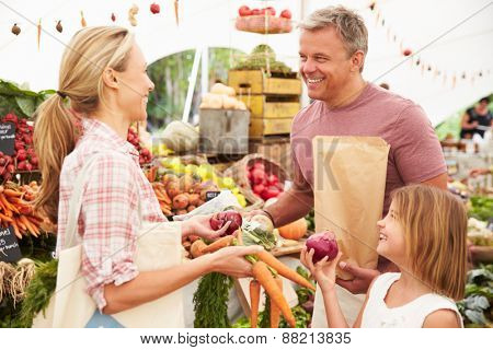 Family Buying Fresh Vegetables At Farmers Market Stall