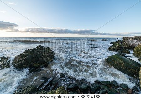 waves crushing over rocks and ruins of old fort at sunset on the beach poster