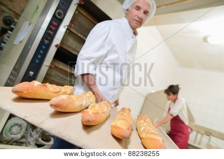 Baker with five baguettes