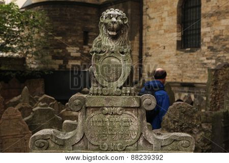 PRAGUE, CZECH REPUBLIC - OCTOBER 15, 2012: Visitor walks beside the old tombstone with the statue of the Lion of Judah at the Old Jewish Cemetery in Prague, Czech Republic.
