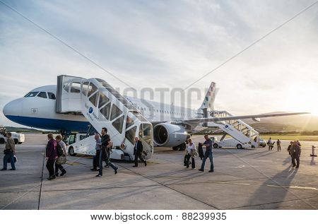 SPLIT, CROATIA - MARCH 6, 2015: Passengers exiting Croatia Airlines' Airbus A320 parked on a runway of Split Airport. This airport is a Europe's main connection to Adriatic coast.
