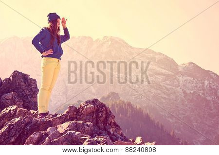 Young beautiful girl standing on the rocks in mountains and looking for new opportunities. Vintage instagram picture. poster
