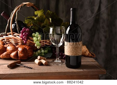 Wine still life on a rustic wood table with warm afternoon window light. An old fashioned cork screw, a basket of grapes and leaves, bread and some corks and an empty wineglass round out the scene.