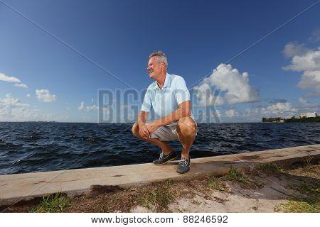 Senior man squatting by the seawall