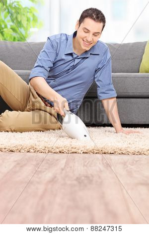 Vertical shot of a young man holding a handheld vacuum cleaner and cleaning a carpet at home