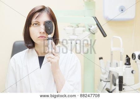 Woman doctor optometrist closed your eye with ophthalmoscope