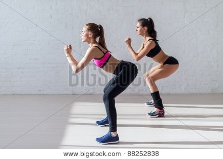 Tough stamina training for two young stunning fitness models doing squats together indoors