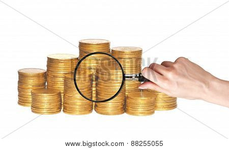 Golden Coins And Hand Holding Magnifying Glass Isolated On White