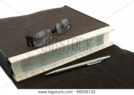 Old Text Book Or Bible With Pen And Eyeglasses And Leather Bag