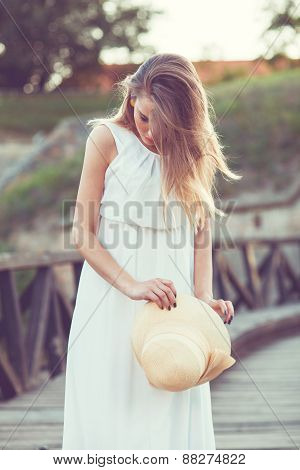Beautiful Young Woman In An Elegant White Dress With A Hat In Her Hand, Standing On A Wooden Bridge