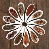 Chinese herbal medicine selection in porcelain dishes over oak background. poster