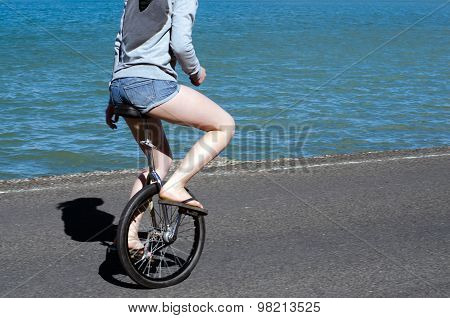 Young woman riding unicycle near the water.