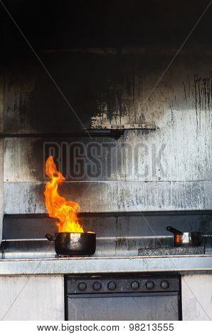 A Kitchen with a stove and pot on fire.