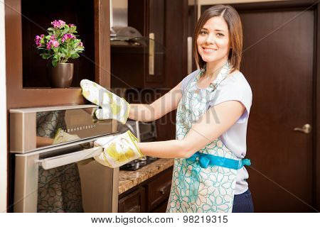 Portrait of a cute young woman wearing an apron and oven mitts opening the oven door poster