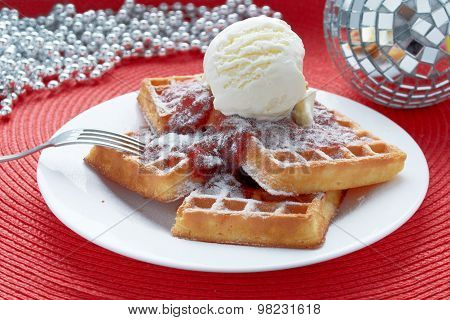 freshly baked Belgian waffles with ice cream and strawberry jam in a white plate on a red table with a mirror balls