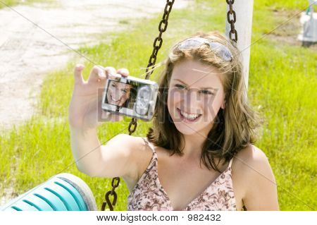 Young Blond Woman Takes A Self Portrait With A Camera