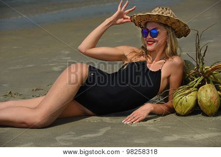 Beautiful woman lying on the tropical beach wearing black swimsuit and hat