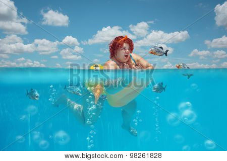 Beautiful young fat woman is swimming with yellow duck lifebuoy and defending oneself against flock of piranhas