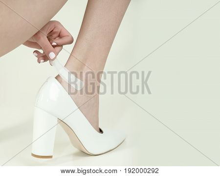 leg with adhesive plaster on female feet with wound in fashionable shoes young girl isolated on white background skincare and health copy space