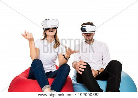 Excited young couple experiencing virtual reality seated on beanbags isolated on white background. A young couple dressed in jeans and white t-shirts