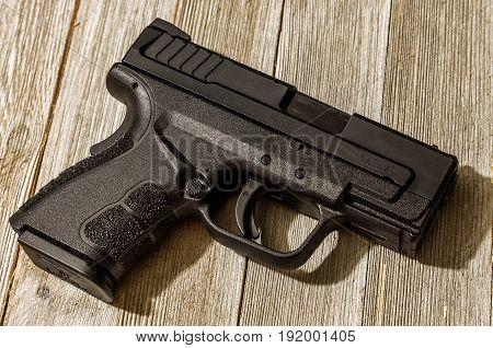 Loaded black 9mm handgun on wood table