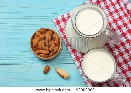 Milk background. Glass jug pitcher of fresh milk with glass, mix almonds, cashew nuts, hazelnut, peanuts, walnuts, pistachio on blue wooden background. Top view with copy space.