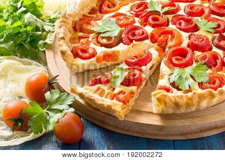 Delicious homemade pie with cheese cottage cheese pepper rolled up in roll in form of flower. Large cake on wooden round plate cherry tomatoes parsley on yellow gauze napkin