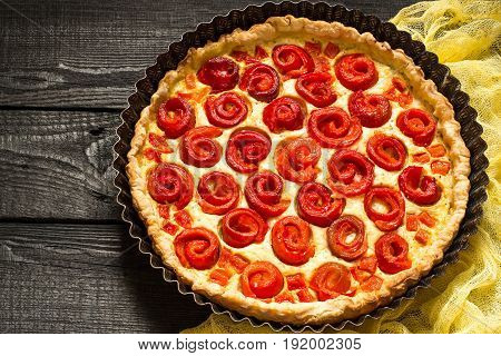 Delicious homemade pie with cheese cottage cheese pepper rolled up in roll in form of flower. Large cake in baking dish on yellow gauze napkin on dark wooden table