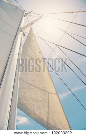 Low angle view of yacht sails and mast against sky