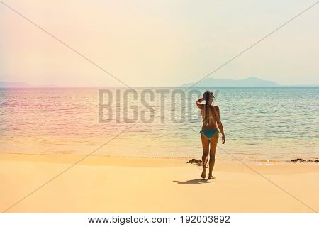 Teenage girl in swimsuit walking to the sea on the tropical beach with a sunlight leak