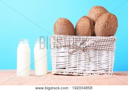 Coconuts In Basket With Bottle Of Milk On Beach Sand