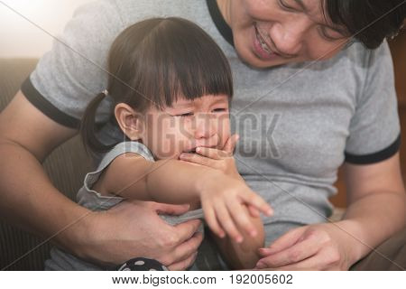 Asian little kid girl crying while father consoling.
