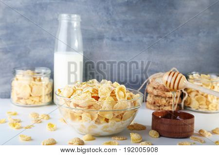 Cornflakes With Milk And Bowl Of Honey On Wooden Table