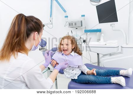 Adorable little girl smiling and looking at camera sitting in dentist chair while dental specialist preparing tools for treatment in a clinic. Little girl sitting in the dentists office