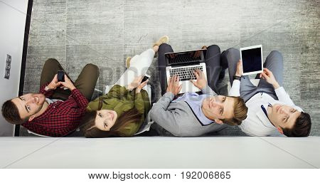 Top view of attractive girls and guy using a laptop, looking at camera and smiling while sitting on the floor
