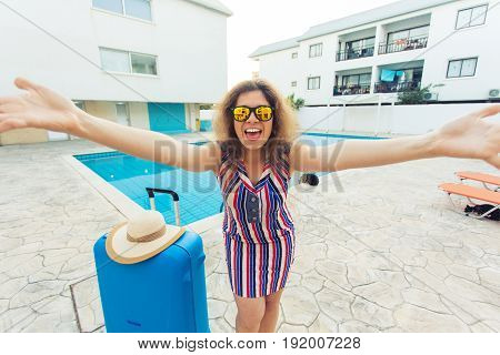 Travel, summer holidays and vacation concept - Beautiful woman near pool area with luggage
