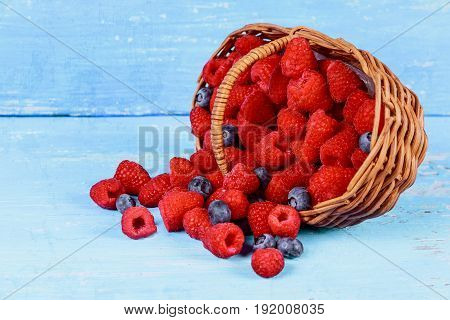 Fresh Berries In An Old Basket. On Wooden Table.