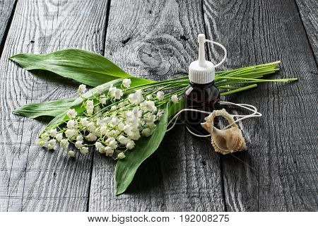 Lilies of the valley (convallaria majalis) and essential oil in vial and aromatic pendant. Aroma of the lily-of-the-valley is actively used in cosmetics production of perfumes hygiene products