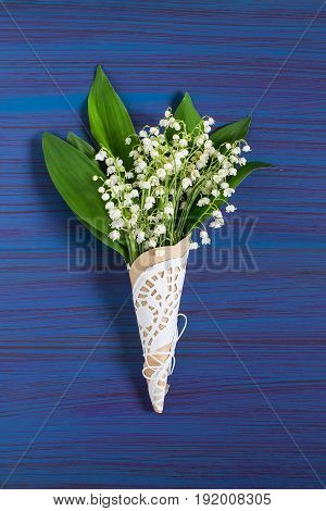 Delicate bouquet of lily of the valley (convallaria majalis) on blue background. Spring flowers: symbol of humility innocence return of happiness