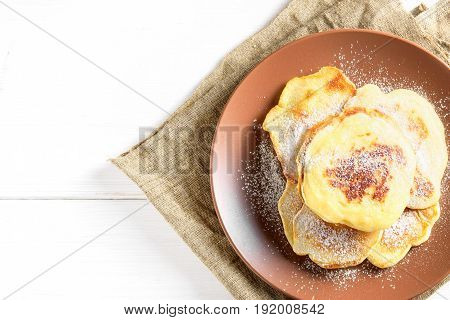 Top view: small pancakes with sugar powder on brown plate over white background. Copy space