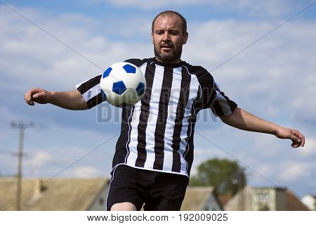 The soccer player is practicing football with ball outdoors.