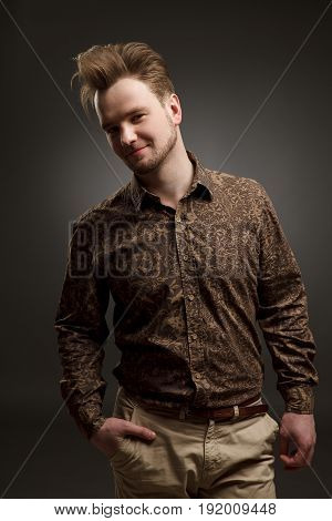 MAN haircut. Stylish young man with trendy hairstyle pose in studio. In shirt with pattern. Vogue. Copy-space