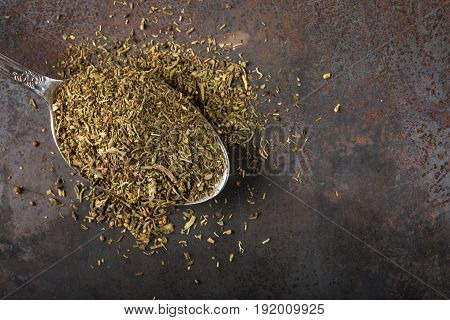 Spoon filled with dried thyme on rusty background with copy space