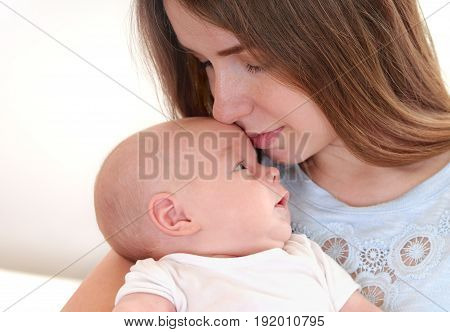 Young mother holding her newborn child. Mom nursing baby. Mother breast feeding baby. Family at home. Happy parenthood
