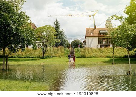 KEHL GERMANY - JUN 18 2016: Couple looking at flooded Rhine river at the border with France. In june large bodies of water has caused inundation of adjacent areas near the river.