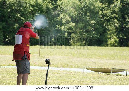 Man shooting skeet with a shotgun. Young man skeet shooting outdoors.