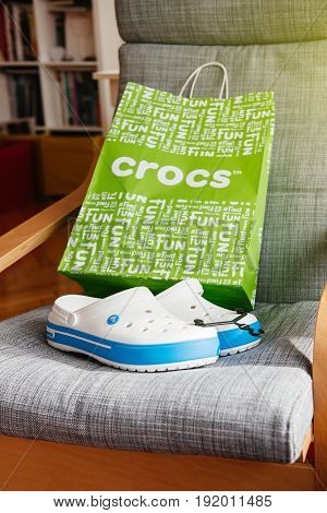PARIS FRANCE - OCT 27 2016: Pair of new Crocs foam clogs on room chair. Crocs is a worldwide company selling comfortable shoes