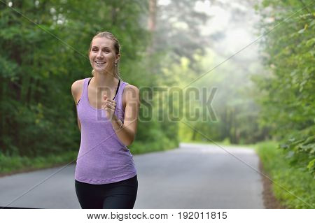 Female runner jogging during outdoor workout in a park. Fitness girl training outdoor. Beautiful young woman running in green park on sunny summer day