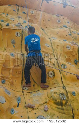 Labuan,Malaysia-May 21,2017:Male athlete with safety equipment climb on yellow climbing wall in Labuan,Malaysia.It is an activity in which participants climb up & across artificial rock walls